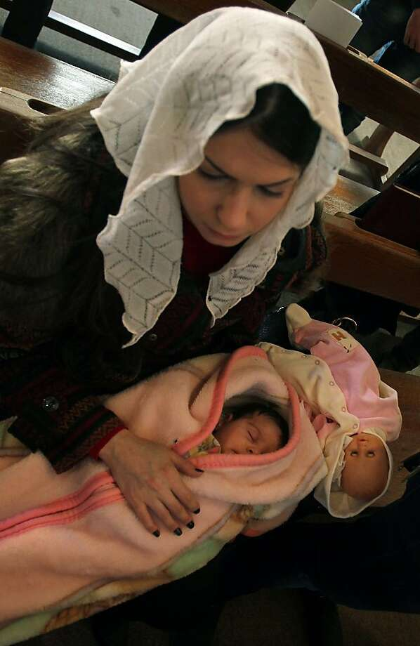 "An Iraqi Christian holds a child as she attends a Christmas mass at the Virgin Mary Chaldean church (Church of Our Lady of Sacred Heart) in the Karrada neighborhood of the capital Baghdad on December 25, 2013. Christians in the Middle East are being ""attacked and massacred"" and driven into exile, the leader of the world's Anglicans Justin Welby said in his first Christmas sermon. Photo: Ali Al-saadi"