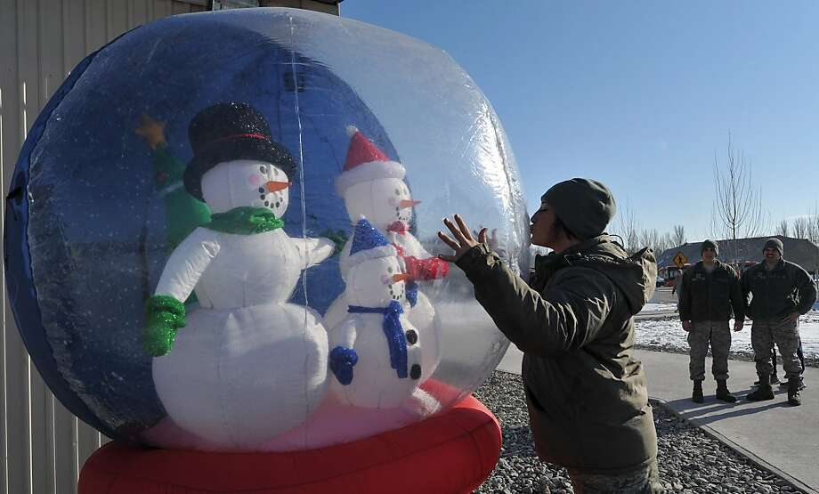 A US soldier kisses an inflatable Snow Dome during Christmas celebration at the US Transit Center of Manas, 30 km from Bishkek on December 25, 2013. Photo: Vyacheslav Oseledko