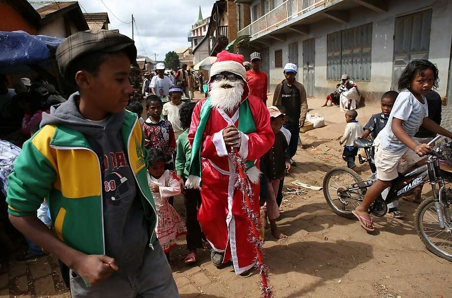 A Madagascar Father Chrismas walks in the dusty street of Ambohibary, 150km from Antananarivo, greeting children on December 25, 2013, days after Madagsacar went to th polls to vote  in a Presidential  election . Observers certified Madagascar's run-off presidential polls as free, credible and democratic on Sunday, urging bickering candidates to stay calm as counting continued after the vote to restore democracy. Photo: Alexander Joe