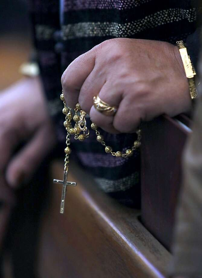 An Iraqi Christian holds a rosary during a Christmas mass at the Virgin Mary Chaldean church (Church of Our Lady of Sacred Heart) in the Karrada neighborhood of the capital Baghdad on December 25, 2013. Photo: Ali Al-saadi