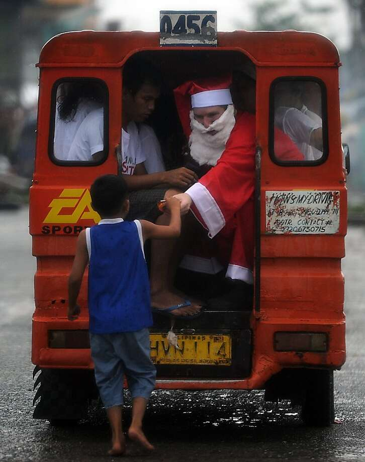 A foreign-volunteer dressed as Santa Claus distributes goodies during Christmas day to children-survivors of the super Typhoon Haiyan in the streets of Tacloban city, Leyte province, on December 25, 2013.  Survivors of the Philippines' deadliest typhoon spent a gloomy Christmas Day surrounded by mud December 25 as heavy rain drove many inside their flimsy shelters, dampening efforts to retain some holiday cheer in the deeply devout nation. Photo: Ted Aljibe