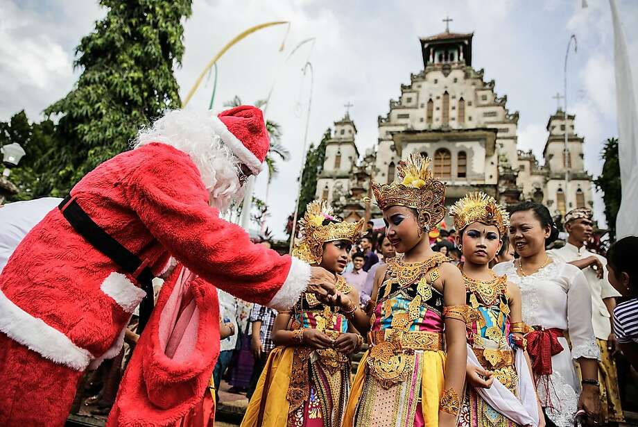 An Indonesian man wearing a Santa Claus costume hands a gift to a dancer during Christmas celebrations at Hati Kudus Yesus Church on December 25, 2013 in Palasari Village, Jembrana, Bali, Indonesia. The village of Palasari comes alive during the Christmas period with extravagant celebrations. Great attention is paid to holiday ornaments and decorations. Men and Women dress up in their finest traditional costumes converging at the famous Sacred Heart church to celebrate the birth of Christ. Photo: Agung Parameswara, Getty Images