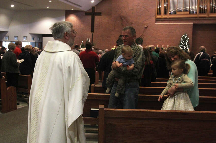 Father Kevin Ryan, left, visits with worshipers before Christmas Mass Wednesday December 25, 2013 at St. Mark the Evangelist Catholic Church. The church is one of the largest Catholic parishes in San Antonio.