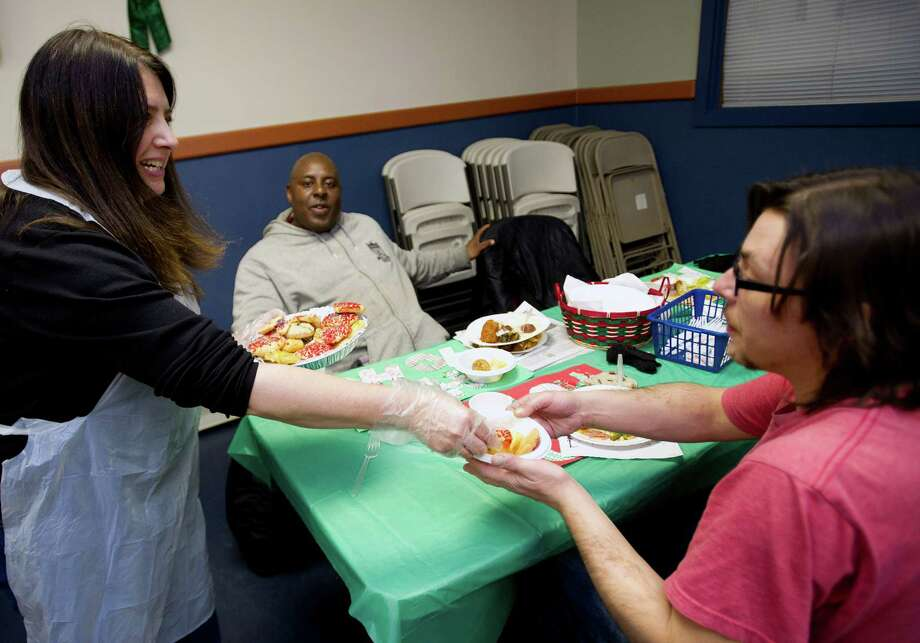 Sharon Franklin-Shavrick, left, serves cookies to Willam Moore, center, and Allan Buttway, right, as she volunteers with Temple Agudath Men's Club as they serve Christmas dinner at Pacific House in Stamford, Conn., on Christmas day, Wednesday, December 25, 2013. Photo: Lindsay Perry / Stamford Advocate