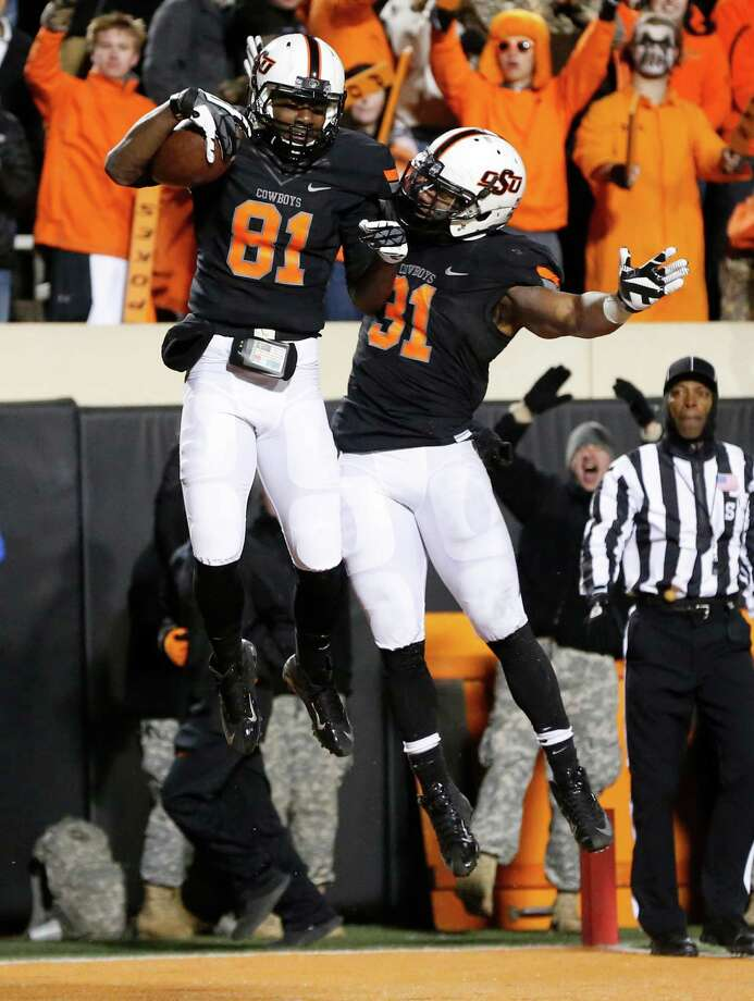 Oklahoma State's Jhajuan Seales (81) and Jeremy Smith (31) celebrate a touchdown against Baylor in the fourth quarter of an NCAA college football game in Stillwater, Okla., Saturday, Nov. 23, 2013. Oklahoma State won 49-17. (AP Photo/Sue Ogrocki) Photo: Sue Ogrocki, STF / AP