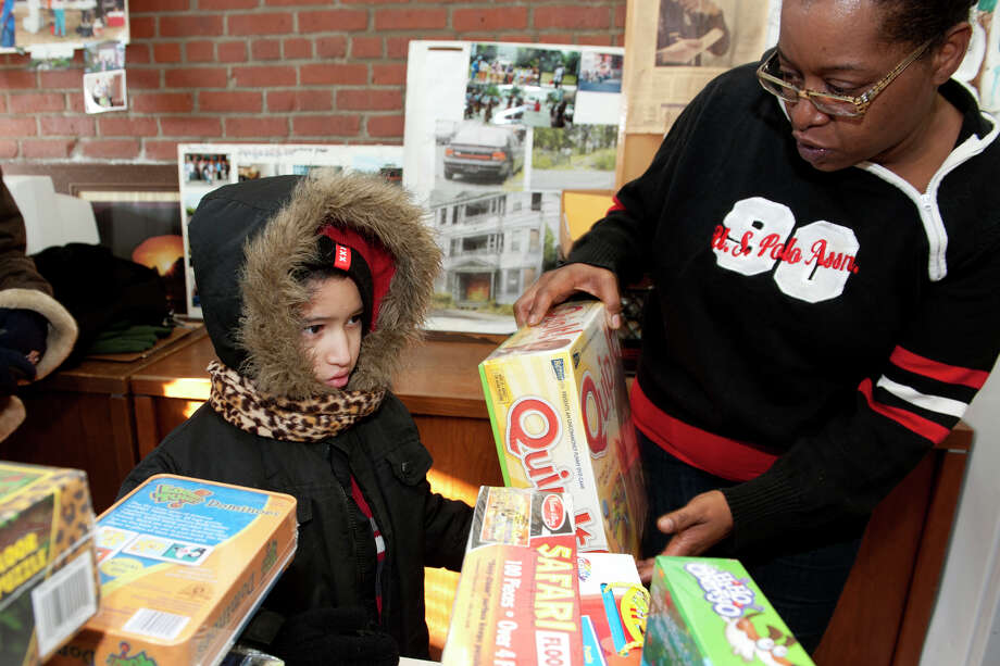 Volunteer Elizabeth Robinson helps Jeremy Serrano, 6, pick out a Christmas gift at the East End Community Council, in Bridgeport, Conn. Dec. 25, 2013. Photo: Ned Gerard / Connecticut Post