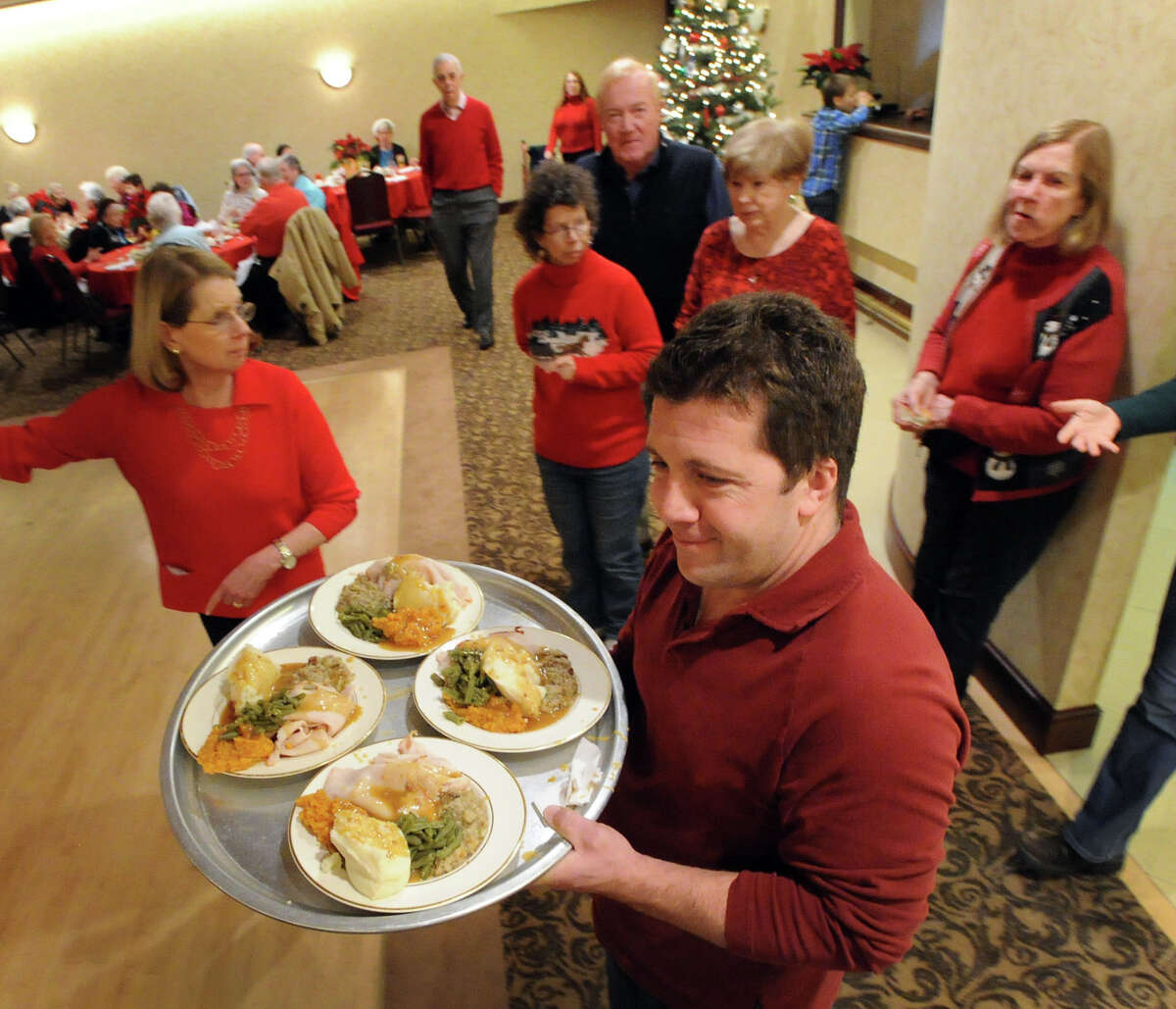 Greenwich Knights of Columbus volunteer Jason Marino carries a tray of turkey dinners during the annual Christmas meal at the club's headquarters on West Putnam Avenue in Greenwich, Christmas Day, Wednesday afternoon, Dec. 25, 2013.