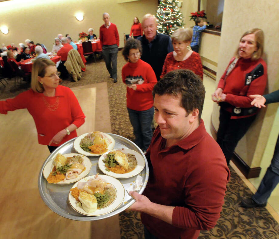 Greenwich Knights of Columbus volunteer Jason Marino carries a tray of turkey dinners during the annual Christmas meal at the club's headquarters on West Putnam Avenue in Greenwich, Christmas Day, Wednesday afternoon, Dec. 25, 2013. Photo: Bob Luckey / Greenwich Time