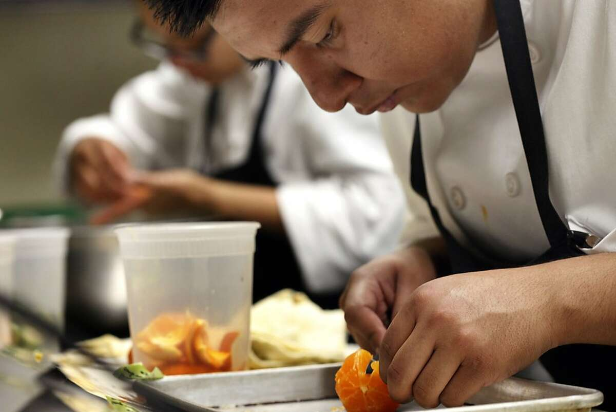 Line cook Andrew Ramos slice mandarins to go with a dinner entree, Friday December 20, 2013, at the Aziza Restaurant in San Francisco, Calif.