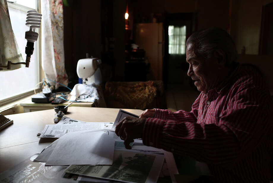 Herbie Hinojosa looks through stories and photographs about his career as a jockey at his home in Brownsville on Wednesday, Nov. 13, 2013. Photo: Lisa Krantz, San Antonio Express-News / San Antonio Express-News
