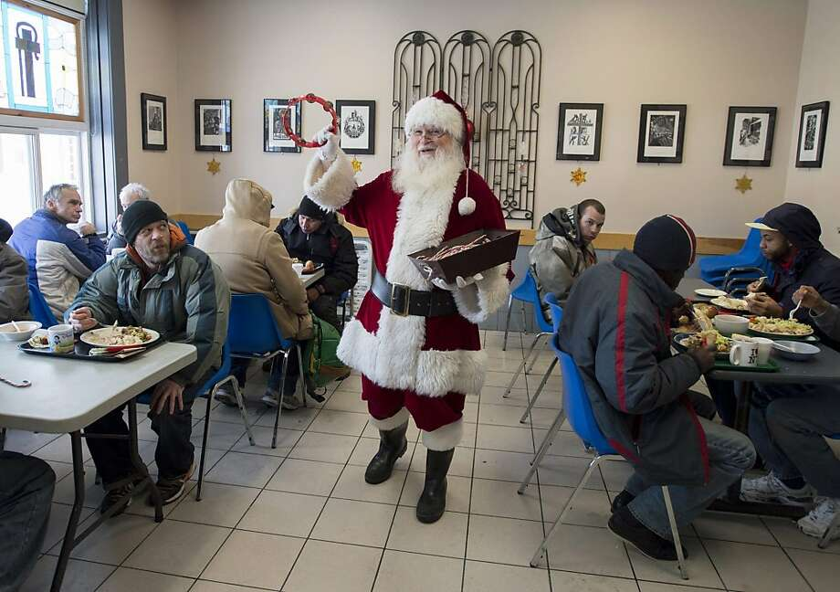 Raymond Tremblay, dressed as Santa Claus, greets clients and hands out candy canes during Christmas day lunch at the Shepherds of Good Hope in Ottawa, Ontario on Wednesday, Dec. 25, 2013. Photo: Justin Tang, Associated Press