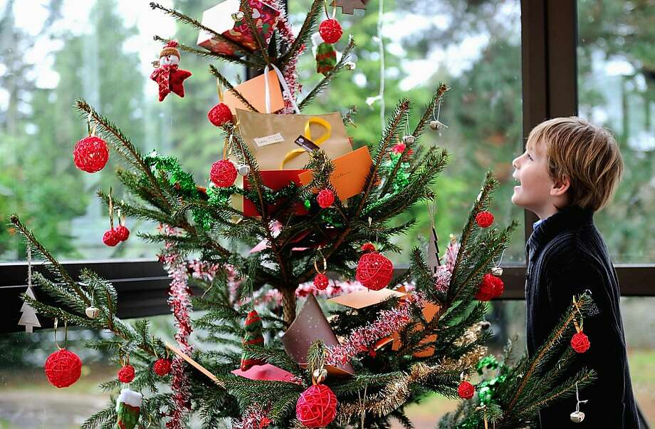 A young boy discovers his presents on the Christmas tree on December 25, 2013 in Dinan, northwestern France. Photo: Philippe Huguen, AFP/Getty Images