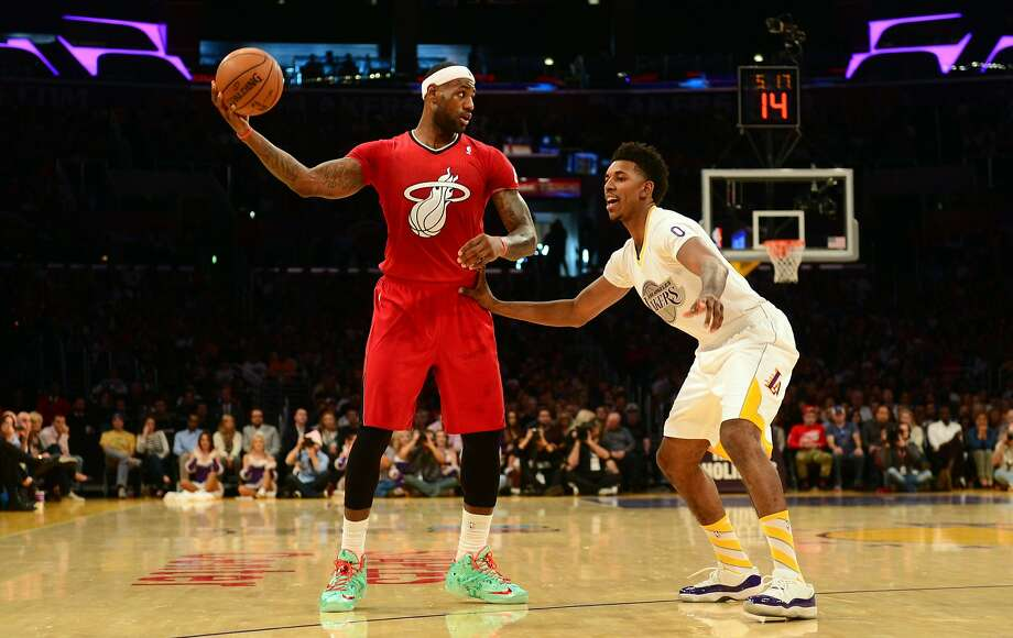 Lebron James (L) of the Miami Heat looks to pass under pressure from Nick Young of the Los Angeles Lakers during their Christmas Day matchup at Staples Center in Los Angeles, California on December 25, 2013.  Photo: Frederic J. Brown, AFP/Getty Images