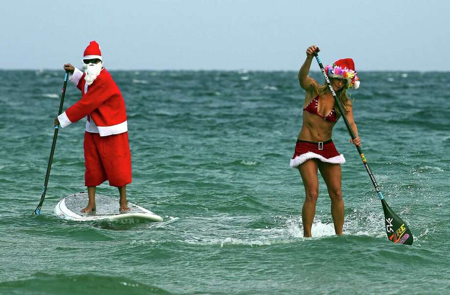 Santa and Mrs Claus, aka Roray Kam and Victoria Burgess, ride the waves off of Ft. Lauderdale, Fla., on Christmas Eve on Tuesday, Dec. 24, 2013. Photo: Mike Stocker, McClatchy-Tribune News Service / Sun Sentinel