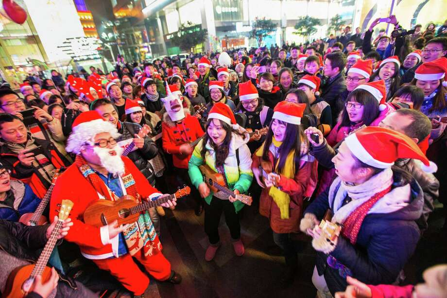 People dressed in Santa Claus costumes attend a celebration for the Christmas Eve at Xinjiekou on December 24, 2013 in Nanjing, China. Photo: ChinaFotoPress, Getty Images / 2013 Getty Images