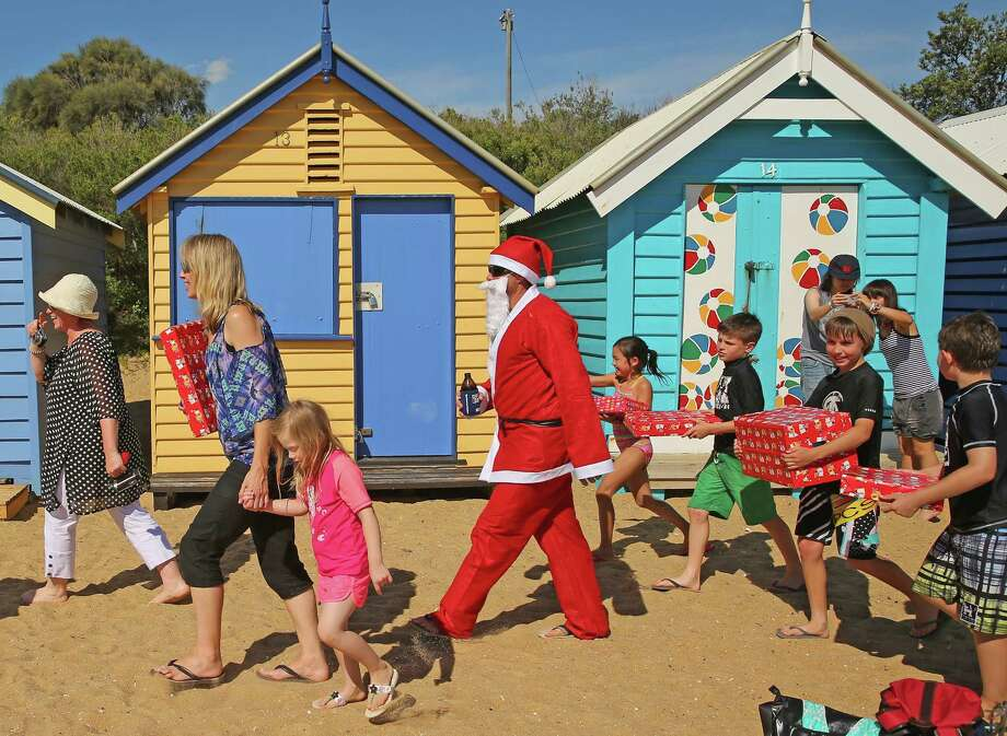 Santa Claus holds a beer as he walks with children holding their Christmas presents on Christmas Day at Brighton Beach on December 25, 2013 in Melbourne, Australia.  Brighton Beach features 82 colourful bathing boxes, which are one of the tourist icons of Melbourne. Temperatures in Melbourne on Christmas Day topped thirty degrees celcius. Photo: Scott Barbour, Getty Images / 2013 Getty Images