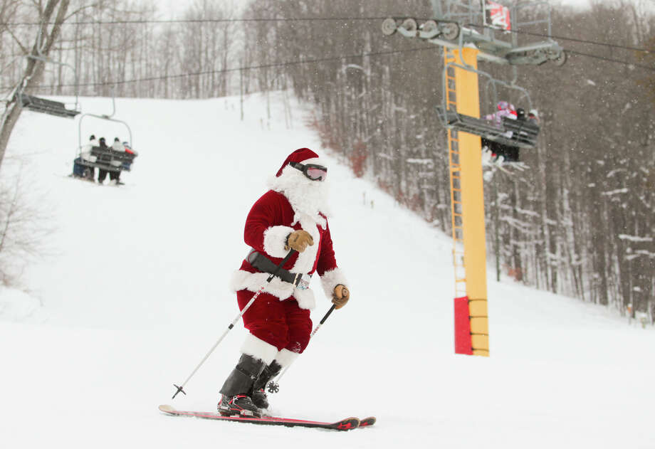 "Santa skis Wednesday, Dec. 25, 2013, during the ""Ski Free With Santa"" event on Schuss Mountain at Shanty Creek Resorts in Bellaire, Mich. Donations of non-perishable food items, clothes and household items for the Father Fred Foundation were encouraged. Photo: Keith King, Associated Press / Traverse City Record-Eagle"