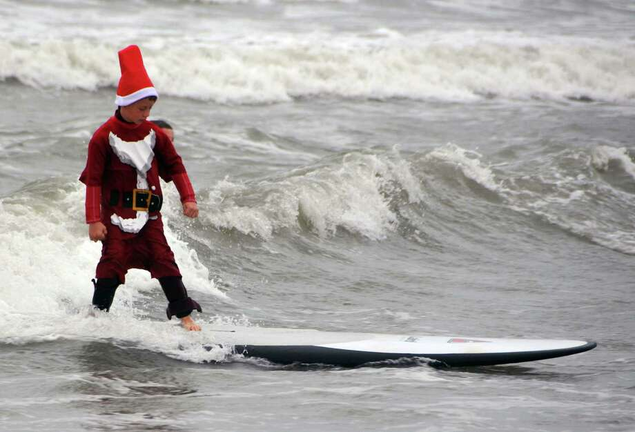 "In this Tuesday, Dec. 24, 2013 photo, a young surfing Santa Claus hits the waves during the fourth annual ""surfing Santas"" event in Cocoa Beach, Fla. Organizer George Trosset said he may move the holiday event to downtown Cocoa Beach next year to accommodate growing crowds. He started the tradition in 2009 with a few family members after seeing a television commercial featuring people surfing in Santa Claus attire. Photo: Malcolm Denemark, Associated Press / Florida Today"