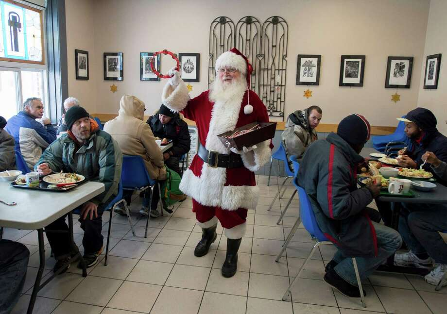 Raymond Tremblay, dressed as Santa Claus, greets clients and hands out candy canes during Christmas day lunch at the Shepherds of Good Hope in Ottawa, Ontario on Wednesday, Dec. 25, 2013. Photo: Justin Tang, Associated Press / CP