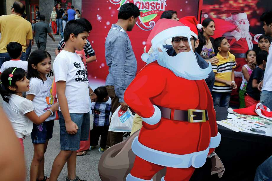 An Indian child poses for a photograph with a cut out poster of Santa Claus as other children wait for their turn, during Christmas Day celebrations at a mall in Mumbai, India, Wednesday, Dec. 25, 2013. Christmas is a national holiday in India, marked by millions of all religions and faiths. Photo: Rajesh Kumar Singh, Associated Press / AP