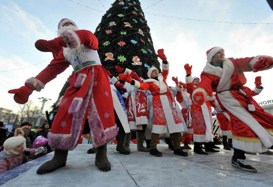 Men wearing  costumes of Ded Moroz (Grandfather Frost), the Santa Claus in Russia, Belarus and Ukraine, dance during their parade in Minsk on December 25, 2013. Photo: VIKTOR DRACHEV, AFP/Getty Images / AFP