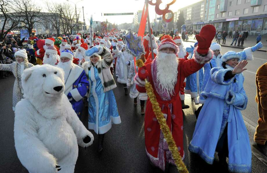 Men wearing  costumes of Ded Moroz (Grandfather Frost), the Santa Claus in Russia, Belarus and Ukraine, and women wearing costumes of Snegurochka (Snow Maiden), the traditional companion of Ded Moroz, march during their parade in Minsk on December 25, 2013. Photo: VIKTOR DRACHEV, AFP/Getty Images / AFP
