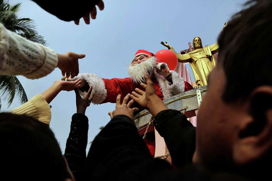 A man dressed as Santa Claus distributes sweets to children on the occasion of Christmas outside a church in Gauhati, India, Wednesday, Dec. 25, 2013. Although Christians comprise only two percent of the population among a Hindu majority, the holiday is observed across the country as an occasion to celebrate. Photo: Anupam Nath, Associated Press / AP