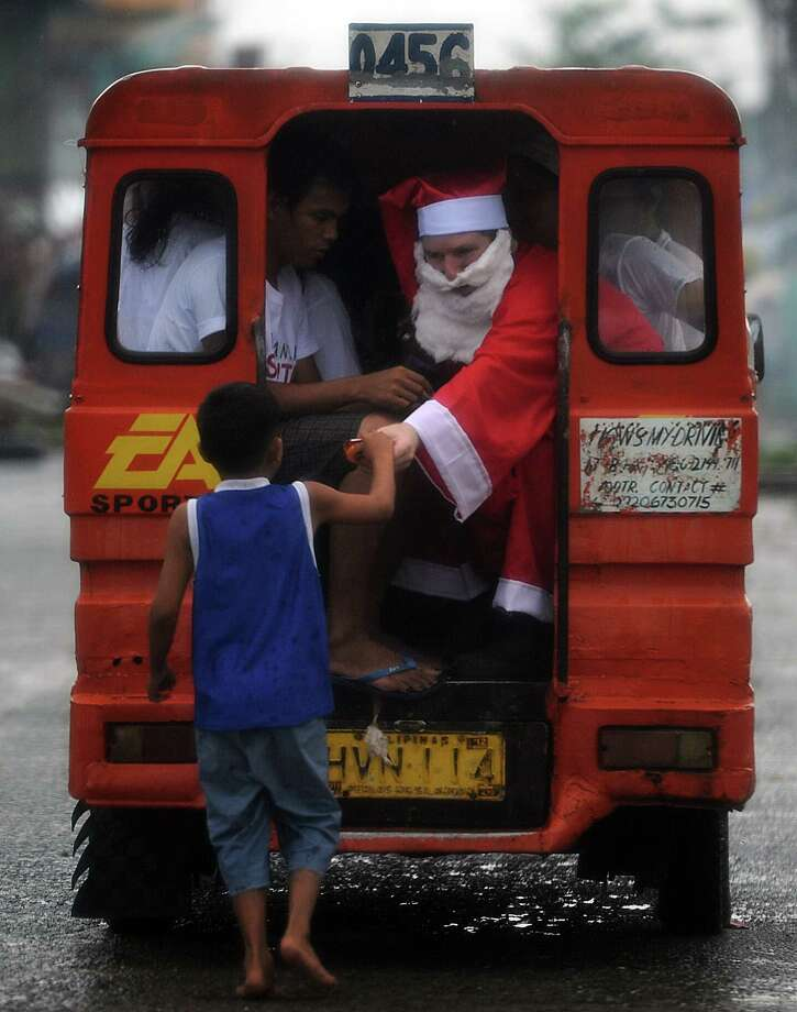 A foreign-volunteer dressed as Santa Claus distributes goodies during Christmas day to children-survivors of the super Typhoon Haiyan in the streets of Tacloban city, Leyte province, on December 25, 2013.  Survivors of the Philippines' deadliest typhoon spent a gloomy Christmas Day surrounded by mud December 25 as heavy rain drove many inside their flimsy shelters, dampening efforts to retain some holiday cheer in the deeply devout nation. Photo: TED ALJIBE, AFP/Getty Images / AFP