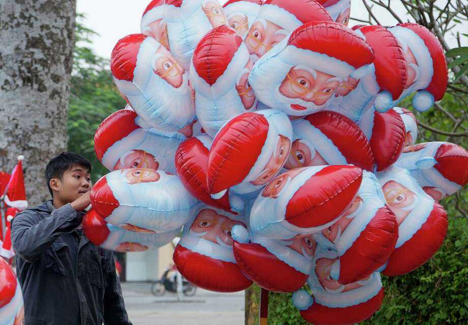 "A street vendor sells ""Santa"" balloons on a street corner in Hoi An, Vietnam, Wednesday, Dec. 25, 2013. Photo: Mark Baker, Associated Press / AP"