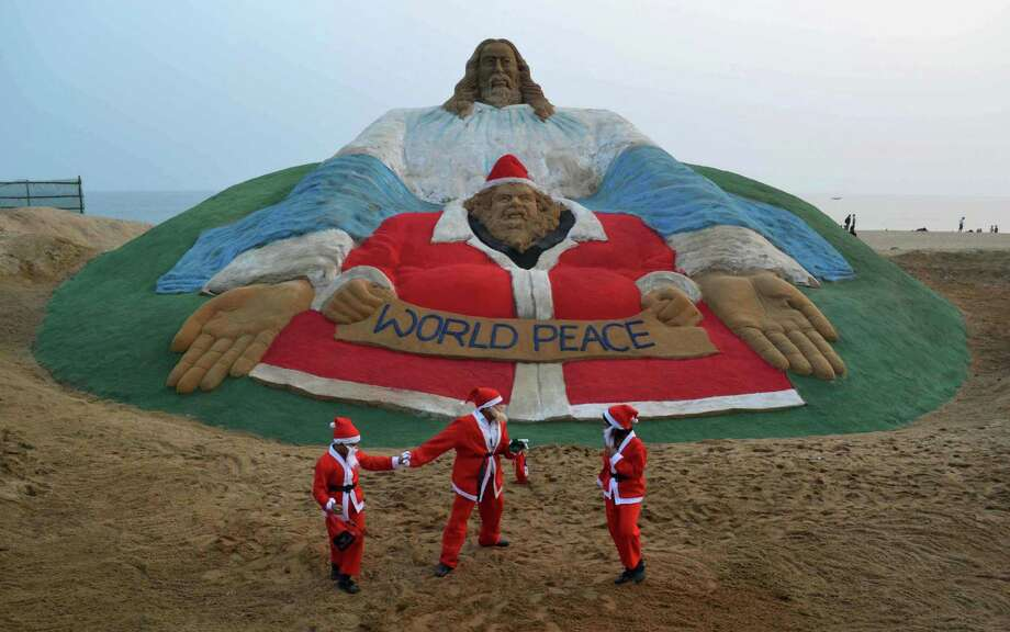 Indian children dressed as Santa Claus play near a sand sculpture depicting God and Jesus Christ, and created by sand artist Sudarsan Pattnaik, at Golden Sea Beach in Puri, some 65 kms away from Bhubaneswar on December 24, 2013. Despite Christians forming a little over 2 percent of the billion plus population in India, with Hindus comprising the majority, Christmas is celebrated with much fanfare and zeal throughout the country. Photo: ASIT KUMAR, AFP/Getty Images / AFP ImageForum