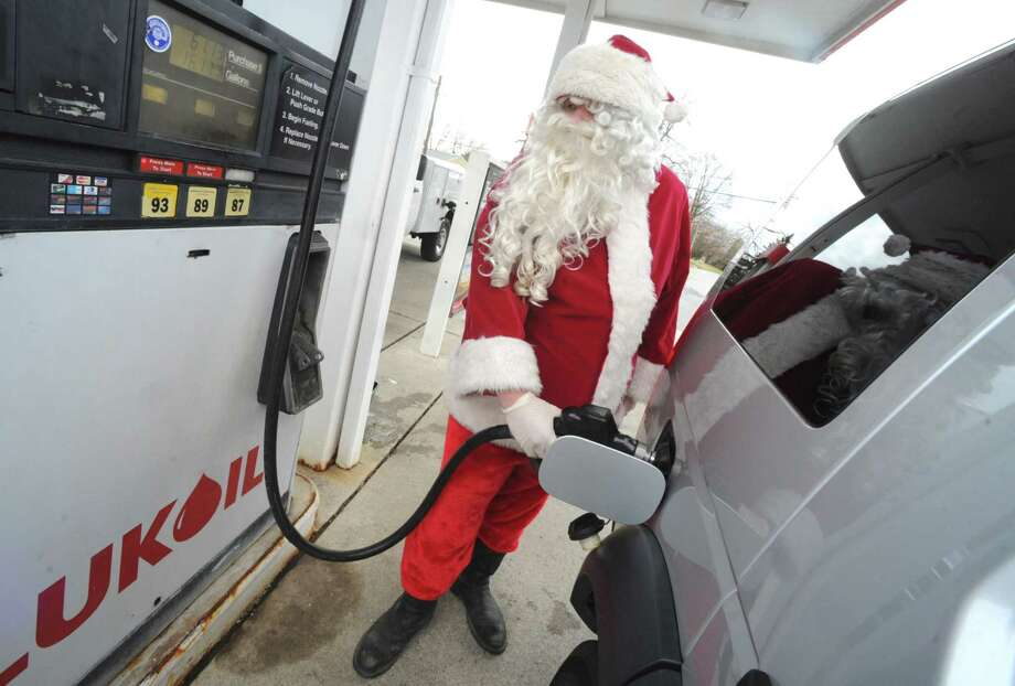 Dressed as Santa, Justin Vegh, of Phillipsburg N.J., pumps gas Tuesday, Dec. 24, 2013, at the Lukoil gas station near Phillipsburg N.J. Photo: Sue Beyer, Associated Press / The Express-Times