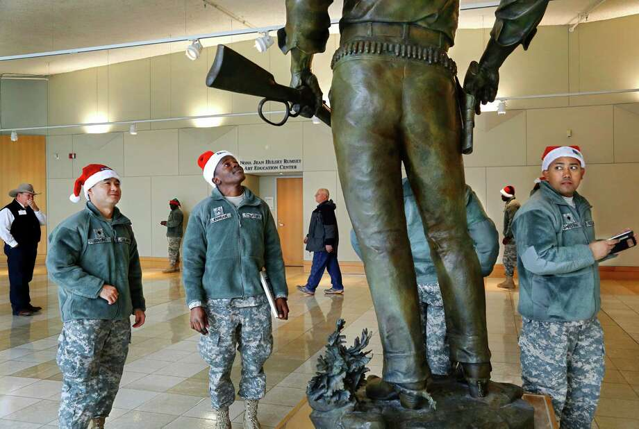 Wearing Santa hats instead of traditional military caps, soldiers pause in front of a larger-than-life statue of American film legend John Wayne by sculptor Edward J. Fraughton during their visit to the National Cowboy and Western Heritage Museum in Oklahoma City on Monday, Dec. 23, 2013. About 150 U.S. Army soldiers stationed at  Fort Sill, who are not from the area and have no family in town, were invited to participate in a Soldiers' Day Out event  Monday. The group toured various local museums, stopped to play games and eat in at an arcade. The outing was hosted by Blue Star Mothers. Photo: Jim Beckel, Associated Press / The Oklahoman