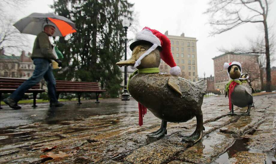 """A man walks past the """"Make Way for Duckling's"""" statues, adorned with Santa hats, during a rain storm in the Boston Public Garden, Monday, Dec. 23, 2013, in Boston. Photo: Charles Krupa, Associated Press / AP"""