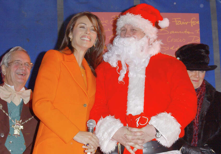 Santa with actress Elizabeth Hurley at the Cirencester Christmas Lights ceremony at Market Place in Gloucestershire, England, on Nov. 21, 2003. Photo: Steve Finn, Getty Images / 2003 Getty Images