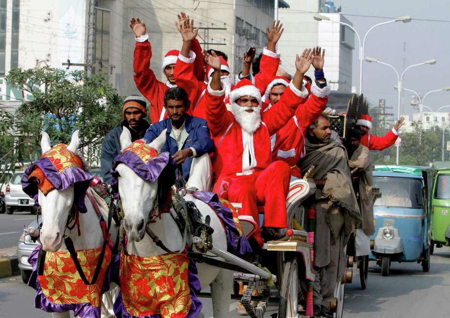 People dressed as Santa Claus ride a horse cart ahead of Christmas celebrations in Lahore, Pakistan, Monday, Dec. 23, 2013. Although Pakistani Christians are in the minority, Christmas is a national holiday and is observed across the country as an occasion to celebrate. Photo: K.M. Chaudary, Associated Press / AP