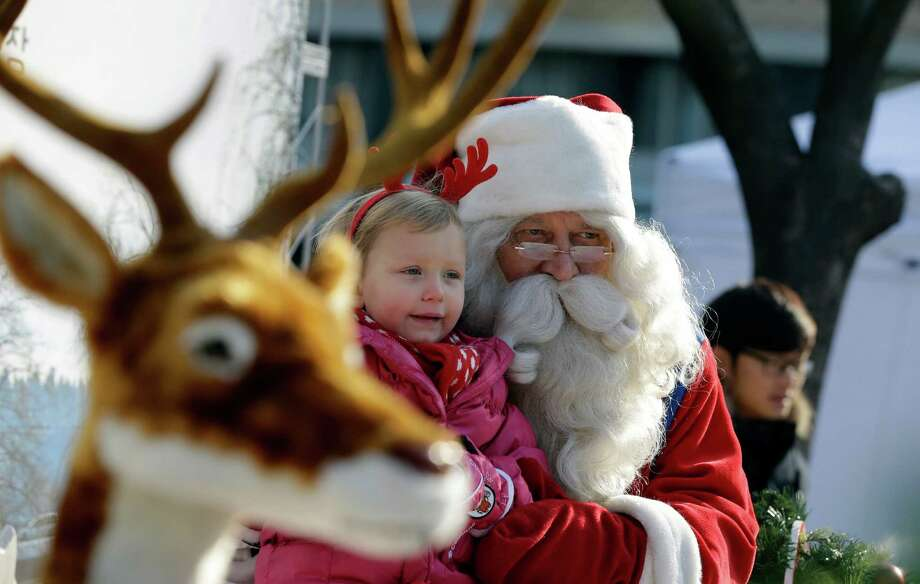 A man from Lapland, Finland dressed as Santa Claus poses with a girl for souvenir photos to celebrate Christmas in downtown of Seoul, South Korea, Monday, Dec. 23, 2013. Christmas is one of the biggest holidays in South Korea, where over half of the population are Christians. Photo: Lee Jin-man, Associated Press / AP