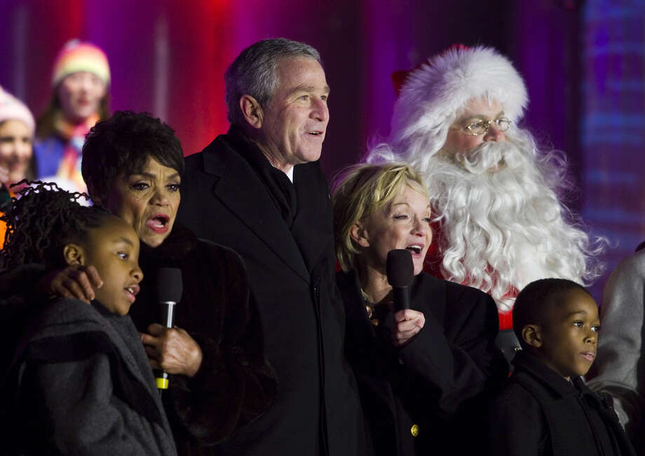 Santa with singer Eartha Kitt and President George W. Bush after the lighting of the National Christmas Tree on the Ellipse in Washington, D.C., on Dec. 7, 2006. Photo: Brendan Smialowski, Getty Images / 2006 Getty Images