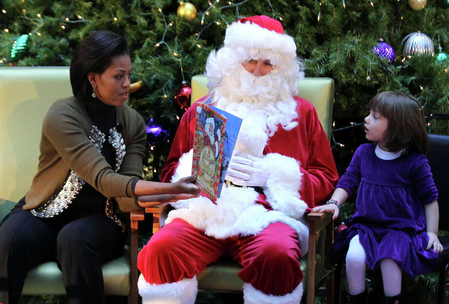 "Santa and First Lady Michelle Obama read the book of ""The Night Before Christmas"" to patients as four-year-old Cheyenne Florio listens during her visit to the Children's National Medical Center in Washington, D.C., Dec. 13, 2010. Photo: Alex Wong, Getty Images / 2010 Getty Images"
