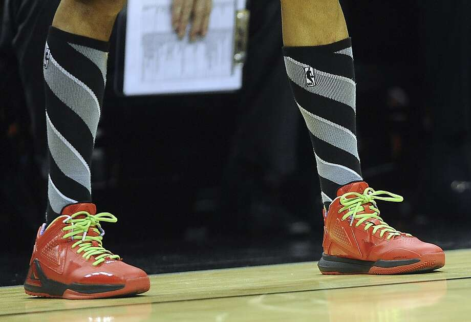 A member of the San Antonio Spours wears special Christmas-style shoes during NBA action at the AT&T Center on Wednesday, Dec. 25, 2013. Photo: Billy Calzada, San Antonio Express-News