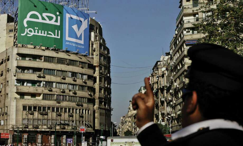 "An Egyptian police major general points towards a sign with Arabic that reads, ""yes to the constitution, Egyptians love their country,"" in Tahrir Square, Cairo, Egypt, Wednesday, Dec. 25, 2013. The constitutional referendum will be held on Jan. 14 and 15, 2014. (AP Photo/Nariman El-Mofty) ORG XMIT: NM101 Photo: Nariman El-Mofty / AP"