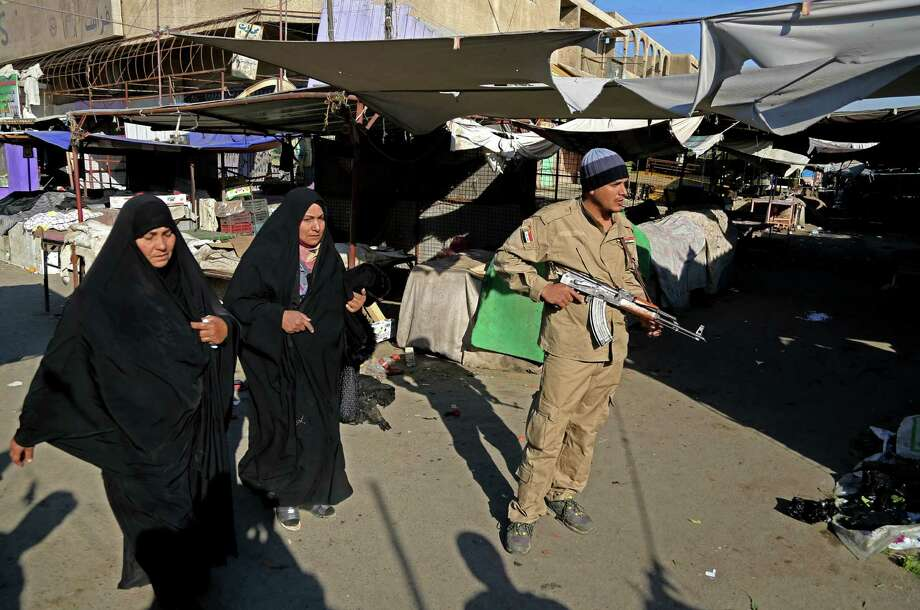 An official stands guard while Iraqi women walk through the site of a bombing in a Christian section of Baghdad. Photo: Karim Kadim / Associated Press / AP
