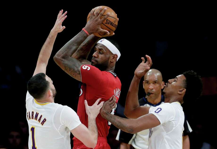 Miami Heat forward LeBron James, middle, is double-teamed by Los Angeles Lakers' Jordan Farmar, left, and Nick Young during the first half of an NBA basketball game in Los Angeles, Wednesday, Dec. 25, 2013. (AP Photo/Chris Carlson) ORG XMIT: LAS105 Photo: Chris Carlson / AP