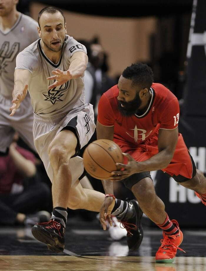 James Harden, right, looks to pass around Spurs guard Manu Ginobili during the first half. Photo: Darren Abate, Associated Press