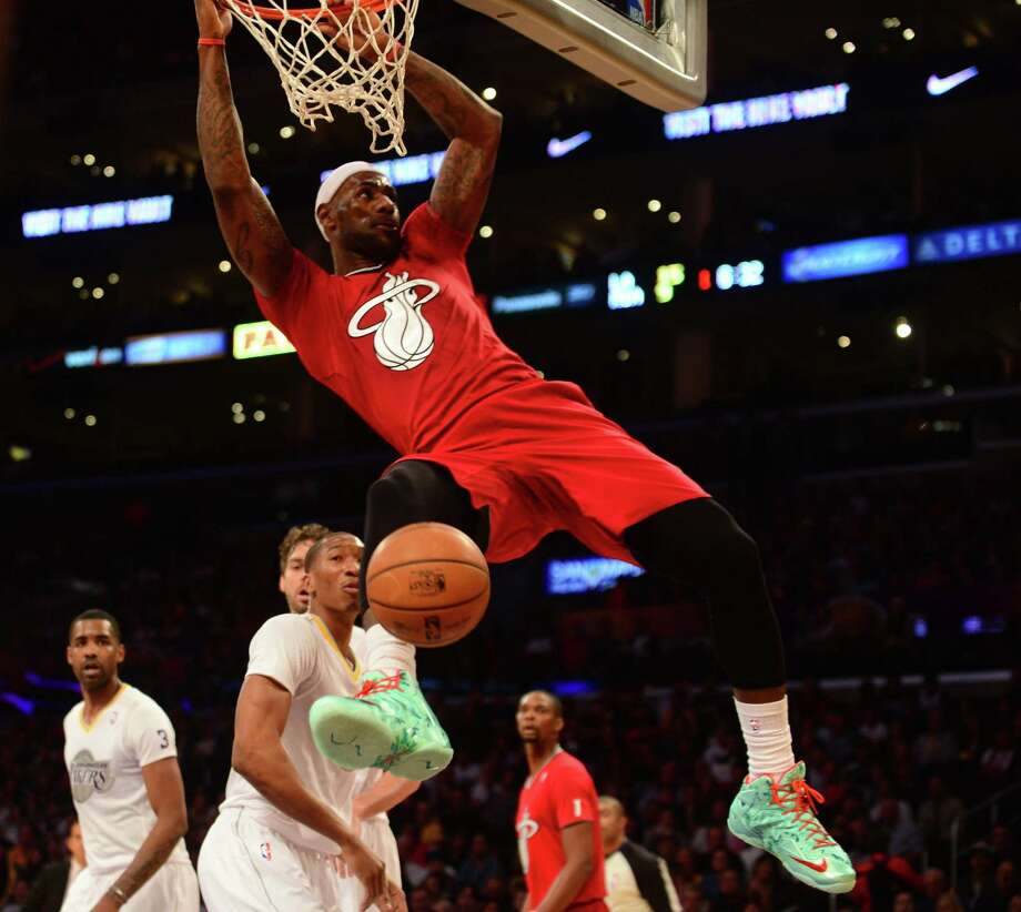 LeBron James completes a dunk against the Lakers in Miami's 101-95 victory at Staples Center. He had 19 points, eight rebounds and four assists. Photo: Frederic J. Brown / Getty Images / AFP