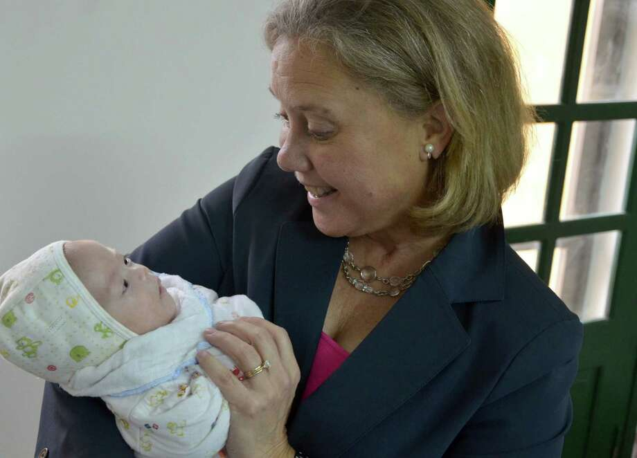 """Sen. Mary Landrieu, D-La., holds an infant during a visit to an orphanage in Vietnam. """"Every child needs and deserves to grow up in a family,"""" she says. Photo: Associated Press / Congressional Coalition on Adopt"""
