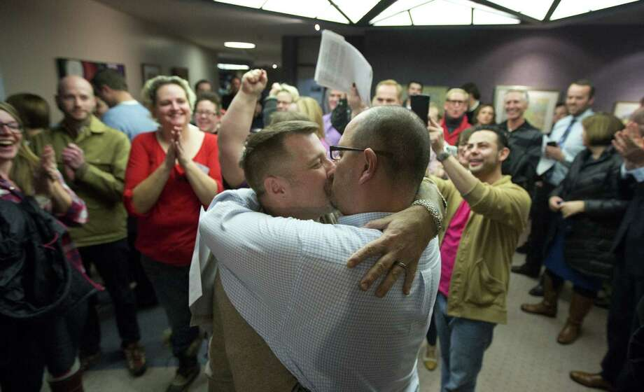 Chris Serrano (left) and Clifton Webb kiss after being married, as people wait in line to get licenses outside of the marriage division of the Salt Lake County clerk's office in Utah. Photo: Kim Raff / Associated Press / FR159054 AP