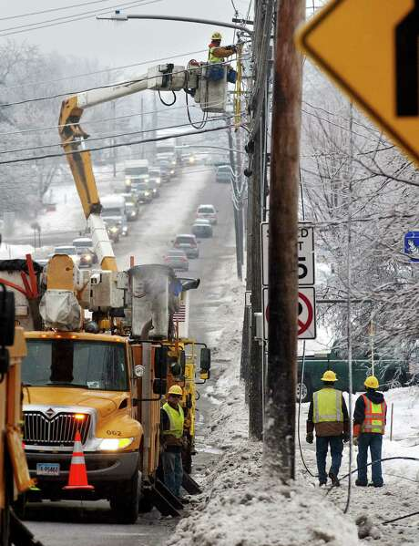 Utility crews respond to a power line brought down by a regionwide ice storm in South Burlington, Vt., Monday. Photo: Glenn Russell / Associated Press / Burlington Free Press