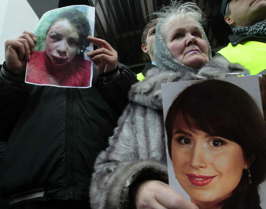 Protesters hold before-and-after photos of journalist Tetyana Chornovol as they rally outside the Ukrainian Interior Ministry in Kiev. Earlier this week, Dmitri Pylypets, a protest organizer in the eastern Ukrainian city of Kharkiv, was beaten and stabbed. Photo: Sergei Chuzavkov, Associated Press / AP