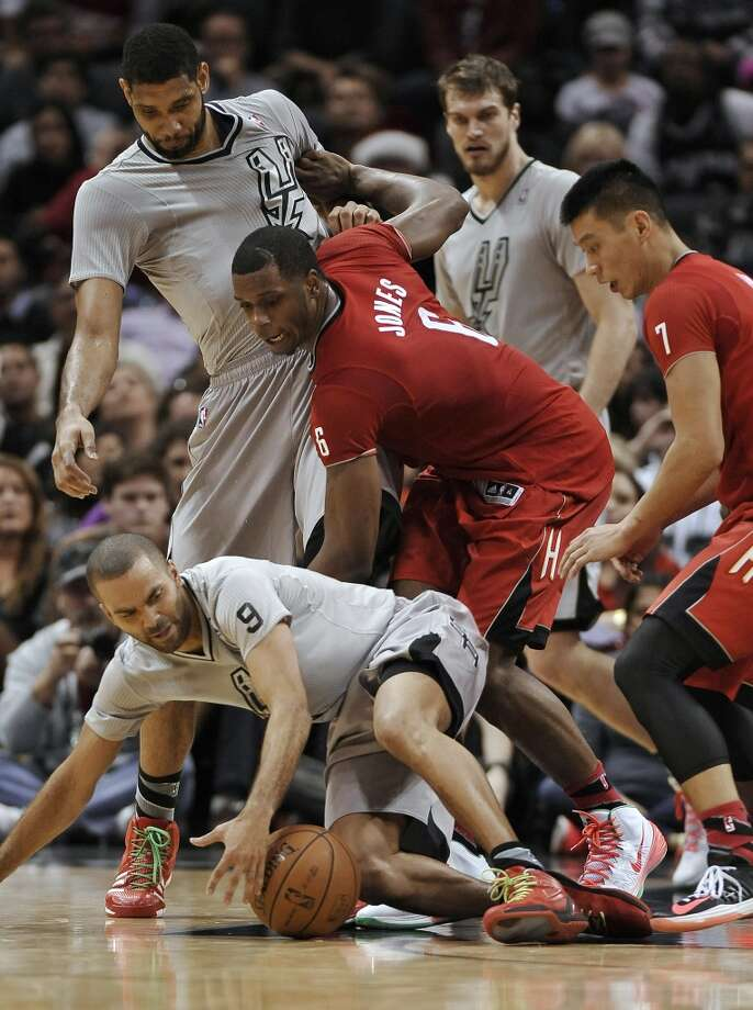 Spurs guard Tony Parker, front left, and Rockets forward Terrence Jones, center, chase a loose ball ahead of Spurs forward Tim Duncan, left rear, and Rockets guard Jeremy Lin, right, during the second half. Photo: Darren Abate, Associated Press