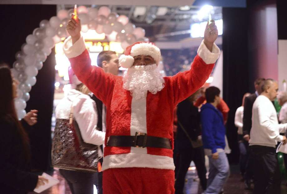 """Miguel Aguilar, from Lytle, Texas, greets fans on the AT&T Center concourse before the Houston Rockets at San Antonio Spurs NBA game on Christmas Day, Wednesday, Dec. 25, 2013. """"I have the Santa suit, and we're season ticket holders, so I said, why not (wear the suit)?"""" he said. Photo: Billy Calzada, San Antonio Express-News"""